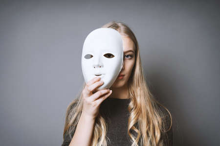 teen girl hiding her face behind mask - identity or personality concept Фото со стока