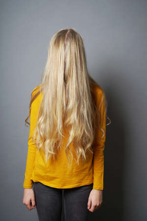 shy young woman with obscured face behind long blond hair - depressed or emabarrassed or indifferent teenage girl Banco de Imagens