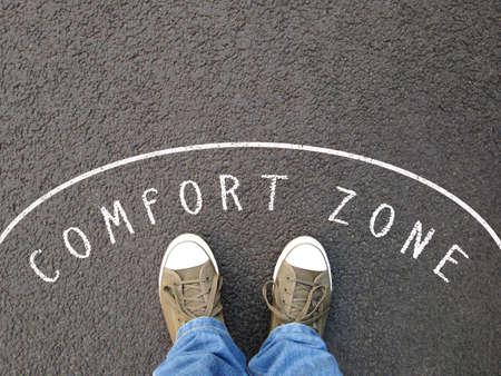 Füße in Canvas-Schuhen, die in der Komfortzone stehen - Fuß-Selfie aus persönlicher Perspektive - Kreidetext auf Asphalt