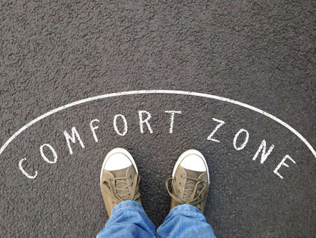 feet in canvas shoes standing inside comfort zone - foot selfie from personal perspective - chalk text on asphalt Stock Photo