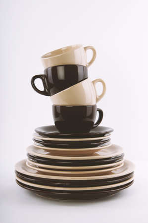 stack of clean dishes in brown and beige - dinner and side plates saucers and cups - mix and match dishware tableware or crockery Фото со стока