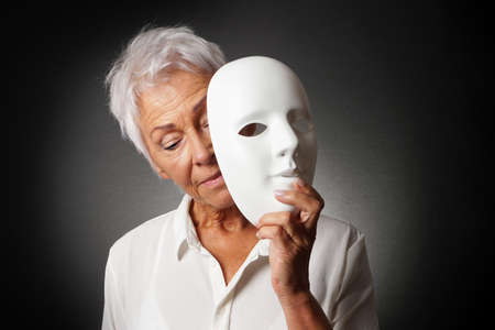 older woman with white hair hiding sad face behind mask - depression or personality concept Stok Fotoğraf