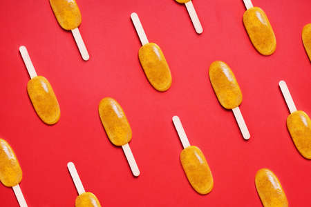 top view passion fruit popsicle or ice lolly or ice pops flat lay pattern on red colored background