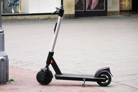 Electric scooter or e-scooter parked on pedestrian street - e-mobility or micro-mobility trend