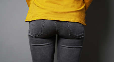 rear view of unrecognizable woman wearing black jeans - female butt or bottom in tight denim pants