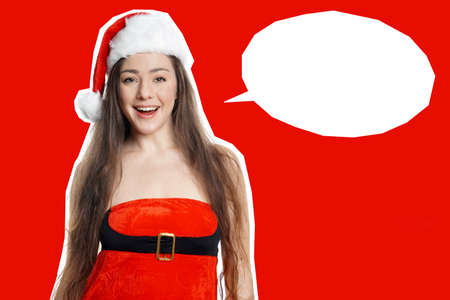 cut out young woman wearing christmas costume dress and santa claus hat on red background with empty speech bubble