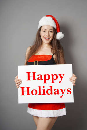 beautiful young miss santa dressed in christmas costume holding sign wishing happy holidays