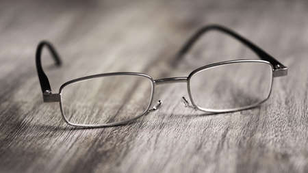 Pair of modern reading glasses or spectacles on rustic wooden table - selective focus with shallow deph of field