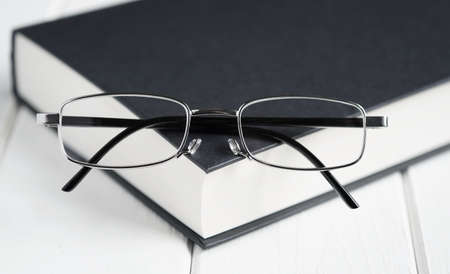 reading glasses or spectacles on top of hardcover book - education and knowledge concept - selective focus with shallow deph of field Фото со стока