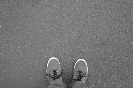 feet in canvas shoes standing on street - foot selfie from personal perspective point of view - asphalt background with copy space Stock Photo