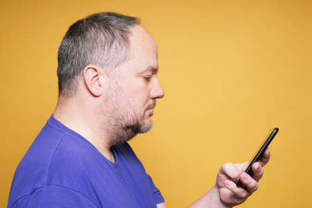 side view of mature man using and looking at smartphone or mobile smart phone reading text message - yellow studio background with copy space