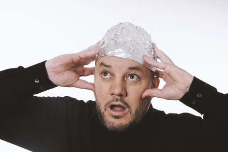 paranoid man wearing tin foil hat as protection against mind control and electromagnetic fields - conspiracy theaory