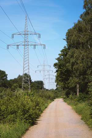 transmission line or overhead power cable with electricity pylons along rural dirt track country lane path through german countryside 版權商用圖片