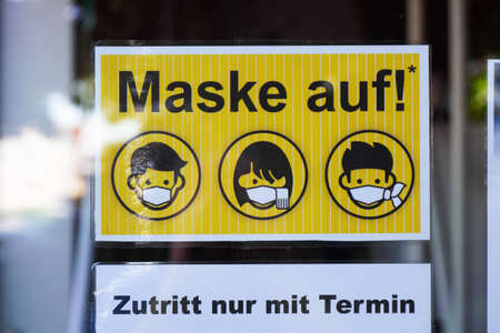 Hannover, Germany - June 1, 2020: German language sign on entrance door to tattoo parlor advises that face mask is mandatory and entry by appointment only.
