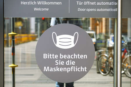 Hannover, Germany - May 21, 2020: German language sign on entrance door to shopping center advises that face mask is mandatory. Editorial