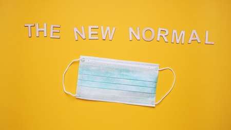 the new normal text with surgical face mask - corona covid-19 concept