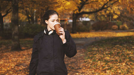 young woman drinking coffee to go from disposable cup while walking in park in autumn