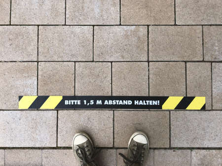 Bitte 1,5 m Abstand halten - German for Please keep 1.5 m distance - line marking on sidewalk - social distancing in Germany