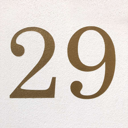 number twenty-nine in arabic numerals - house number 29 in gold paint on wall 版權商用圖片