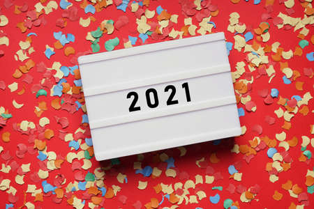 year 2021 lightbox sign on red paper background with confetti - new years eve party celebration concept flat lay