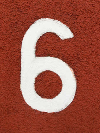 number six in arabic numeral - house number 6 in white paint on red roughcast plaster wall