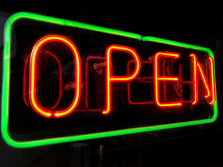 open neon sign in shop or store window at night