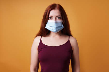 young woman wearing a medical face mask covering mouth and nose - protection against corona virus - studio portrait on orange color background with copy space 版權商用圖片