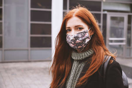 young woman wearing self-made everyday cloth face mask outdoors in city - new normal covid-19 corona virus pandemic concept - real people lifestyle in winter