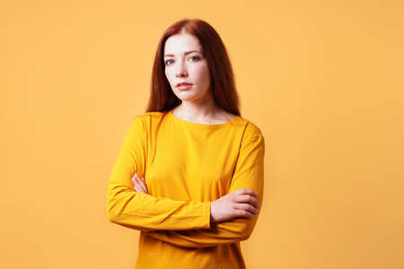 colorful studio portrait of confident young woman with her arms folded - yellow orange color background with copy space