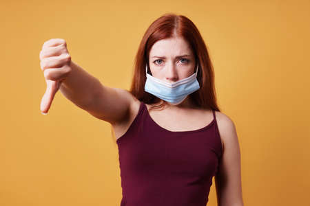 Young woman wearing medical face mask wrong under nose and making thumbs down gesture