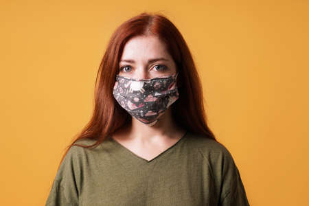 young woman wearing homemade everyday cloth face mask or community mask - covid-19 corona virus pandemic hygiene concept