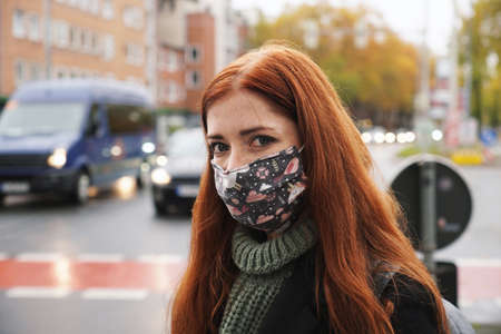 young woman wearing everyday cloth face mask outdoors as pedestrian in busy city traffic, new normal covid-19 corona virus pandemic and air pollution concept, real people lifestyle in winter