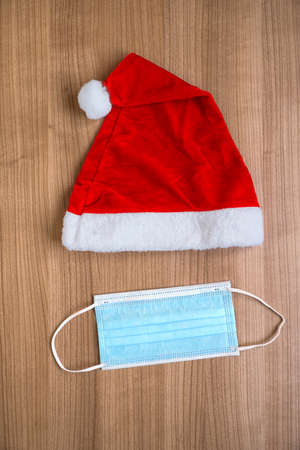 Santa Claus hat and face mask creative minimal concept flat lay of corona Christmas during coronavirus covid-19 pandemic