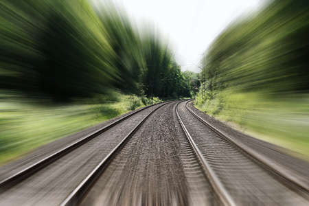 double-track railroad railway or train tracks with speed motion blur - fast travel concept background with copy space