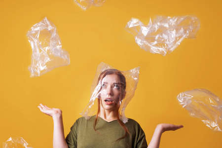 young woman overwhelmed by plastic waste and suffocating from plastic bag over her head - ecology and pollution concept