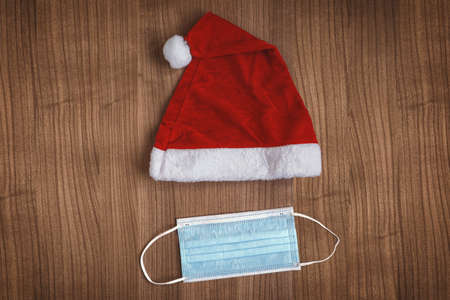 Christmas concept with Santa Claus hat and face mask - creative minimal flat lay - coronavirus covid-19 pandemic