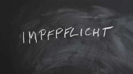 Impfpflicht translates as compulsory or mandatory vaccination in German language - text written in chalk on blackboard