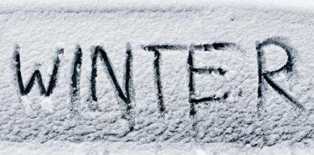 word winter written with finger in fresh snow on car window Standard-Bild