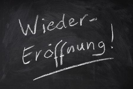 Wiedereroeffnung means reopening in German - handwritten text on chalkboard sign