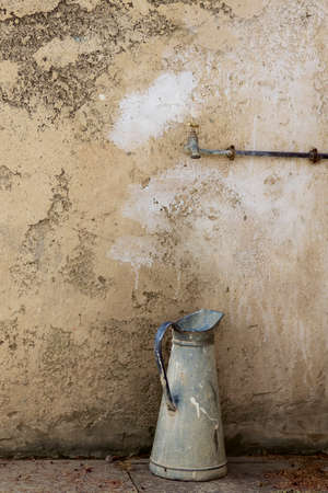 window shade: water pot in front of a stone wall