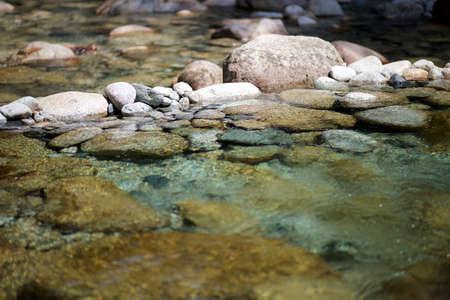 水で素敵な太陽光反射と川の小石 写真素材