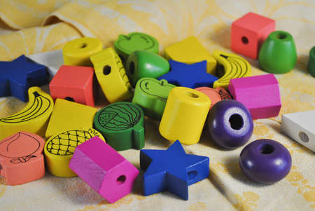 Bright colored beads of wood of different shapes for children's creativity. Star, Apple, pineapple and others Foto de archivo