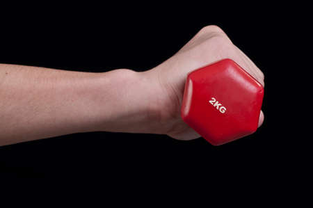 Hand of a young man holding a red dumbbell on a black background