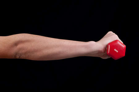 Man hand is holding a red barbell on black background Stock Photo