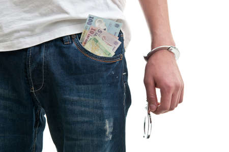 fettered: Man in jeans with handcuffs and money in pocket Stock Photo