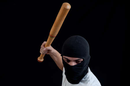 Hooligan with baseball bat ready for fight on black photo