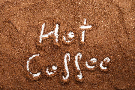 The words hot coffee written against scattered natural coffee photo