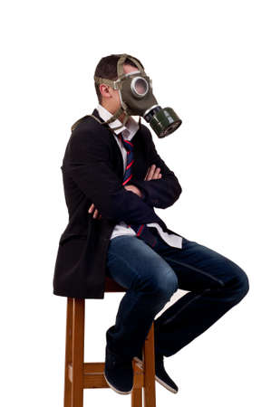 man with gas mask sitting on chair
