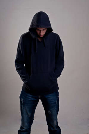 teenager with hoodie looking down against a dirty gray wall photo