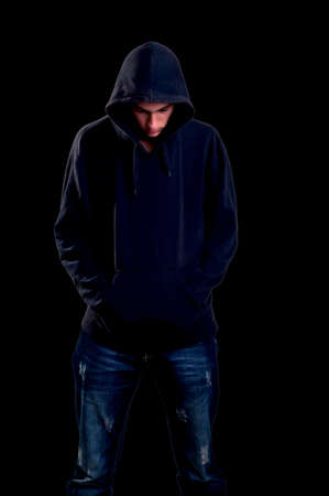 teenager with hoodie looking down on black background Stock Photo